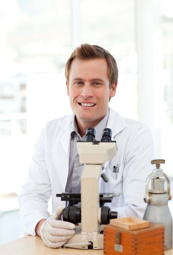 Male scientist looking through a microscope in a laboratory