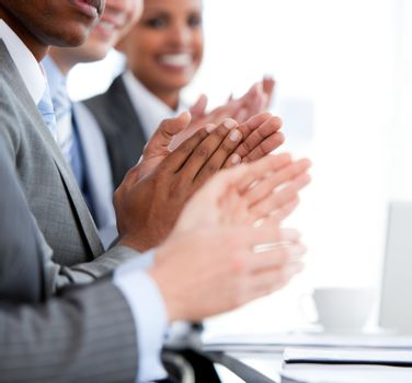 Close up of a  mixed business team applauding a presentation in the office