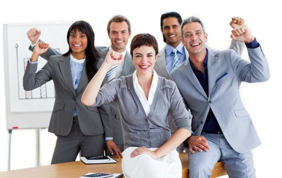 Succesful business team punching the air in celebration in a meeting