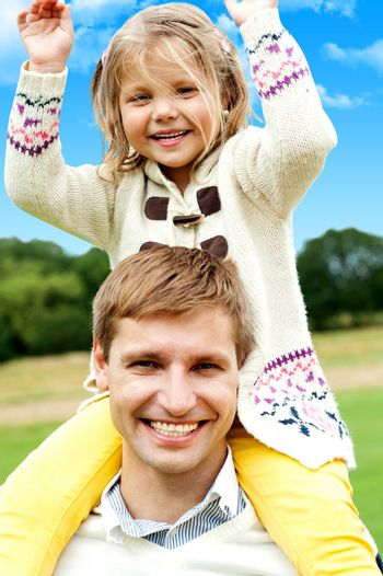 Father and Daughter. Excited girl child enjoying piggyback outdoors