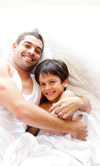 Delighted father and son smiling at camera