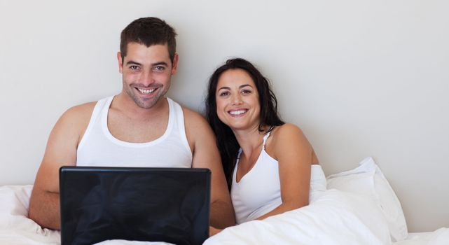 Happy couple in love smiling at the camera using a laptop