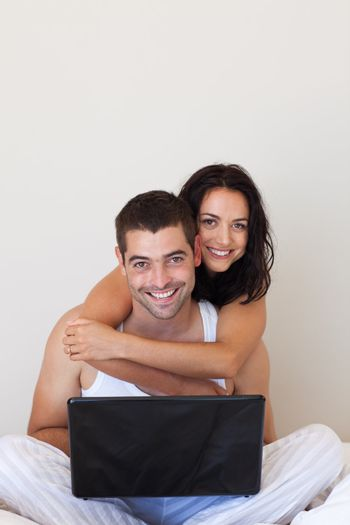 Smiling love couple sitting on bed with laptop