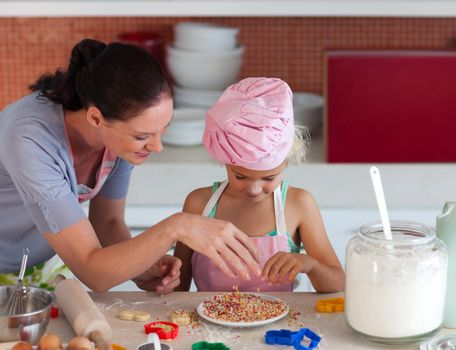 Young mother with her daughter baking