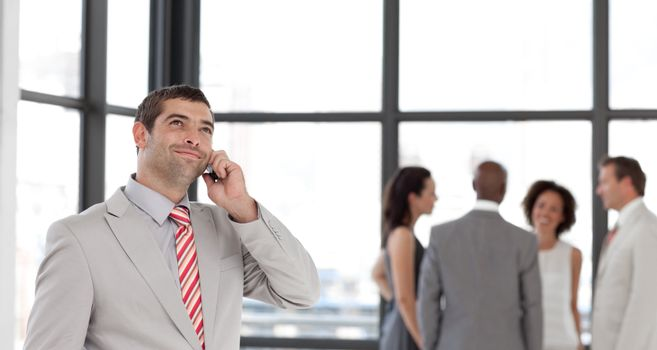 Businessman holding a phone at workplace with his colleagues