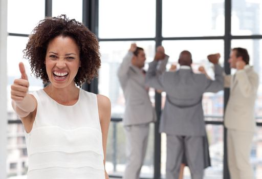 positive Businesswoman doing a thum-up with his colleagues in the background