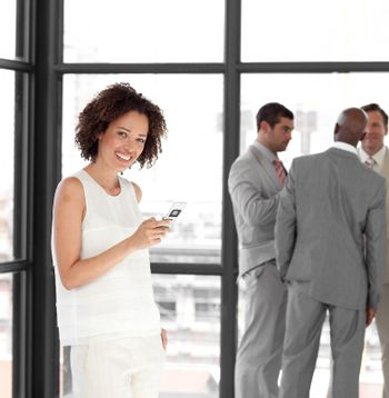 Cheerful Businesswoman holding a phone at workplace with his col