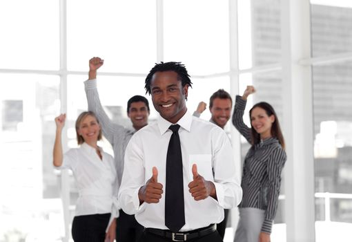 Male manager doing a thumb-up with his team in a office