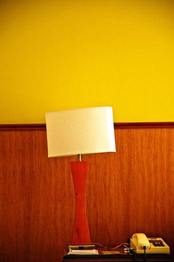 A lamp and telephone on a desk with a yellow and wood wall.