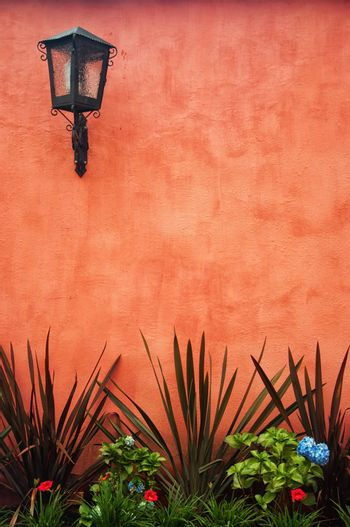 A red colonial wall with a lantern in the upper left.