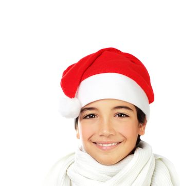 Happy Santa boy smiling, portrait of a cute teen face isolated on white backgroung, kid wearing red Christmas hat, winter holidays celebration