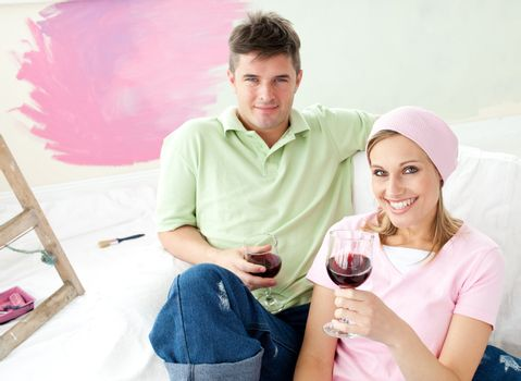 Delighted couple having free time together with a glass of wine