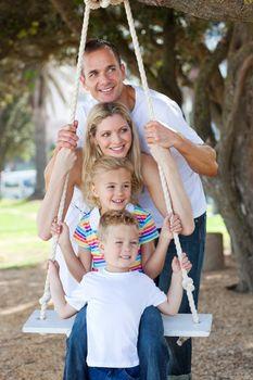 Cheerful family swinging