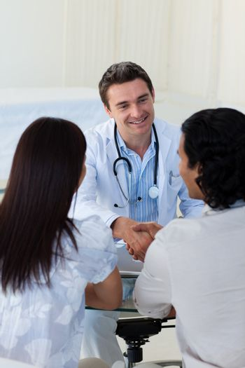 Smiling doctor explaining diagnosis to a couple