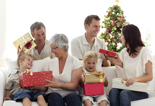 Happy family at home sitting on sofa opening Christmas presents