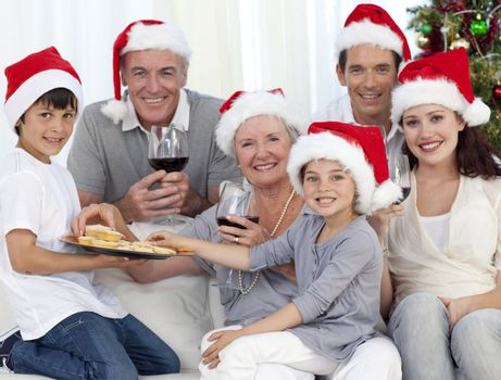 Family drinking wine and eating sweets in Christmas at home