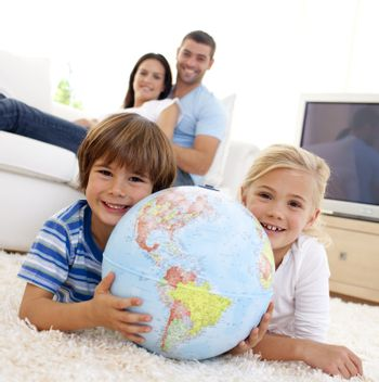 Children playing with a terrestrial globe at home with their parents on sofa