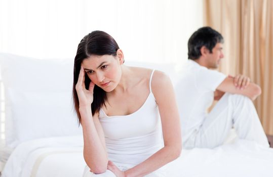Angry couple having an argument sitting on bed