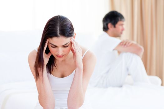 Sad couple having an argument sitting on bed