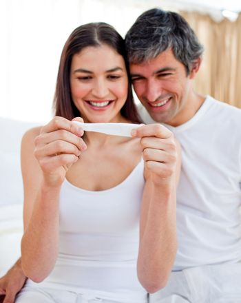 Glowing couple finding out results of a pregnancy test