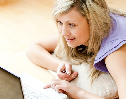 Bright woman shopping on-line lying on a sofa at home