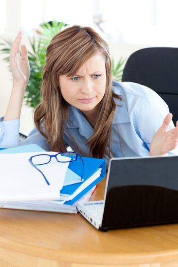 Irritated businesswoman looking at her laptop