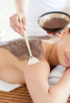 Charming woman enjoying a mud skin treatment