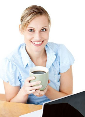 Glowing businesswoman drinking coffee smilng at the camera