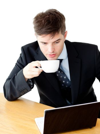 Stressed young businesswoman drinking coffee and using his lapto