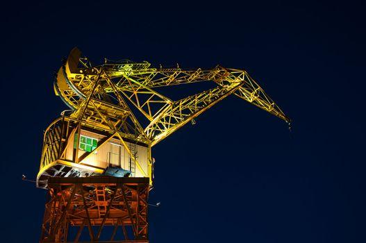 A yellow and orange crane seen at night.