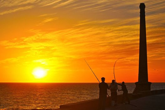 Silhouettes of three men on the coast fishing at sunset.