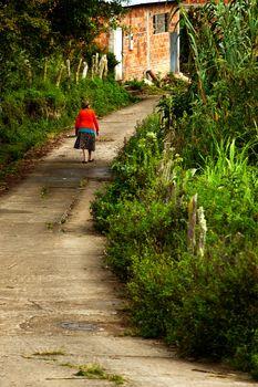 An elderly woman walks down a road in rural South America.
