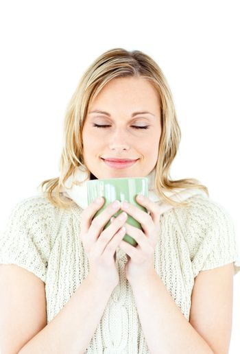 Happy blond woman wearing a pullover and holding a cup of coffee