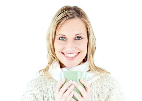 Smiling blond woman wearing a pullover and holding a cup of coff