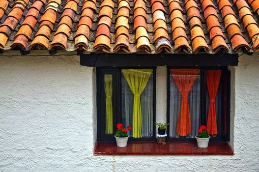A window with a colonial style wall with colorful curtains.