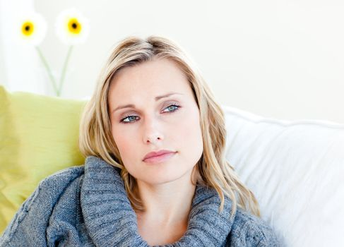 Exhausted woman lying on the sofa with a grey pullover