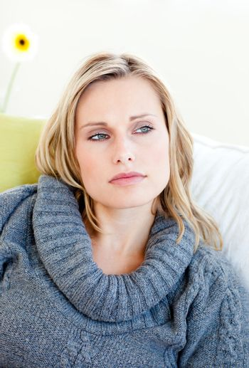 Tired woman lying on the sofa with a grey pullover
