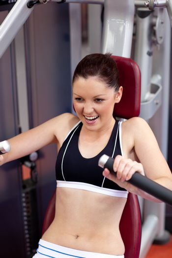Charming athletic woman using a bench press
