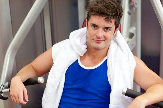 Handsome muscular man using a bench press
