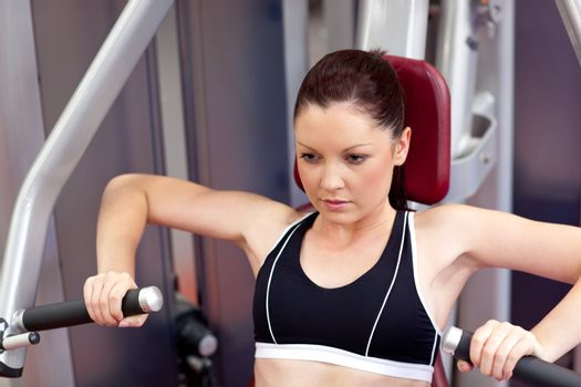 Concentrated athletic woman using a bench press