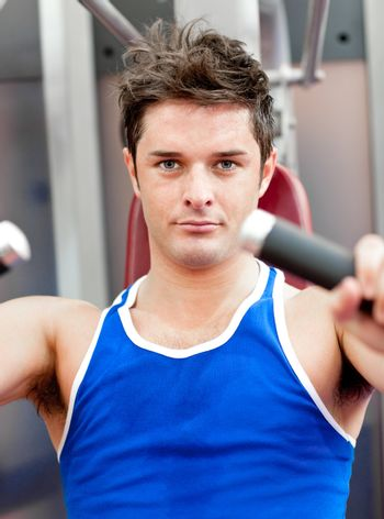 Charming athletic man using a bench press