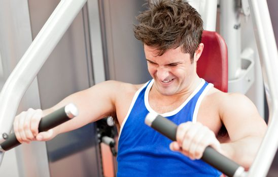 Strong athletic man using a bench press