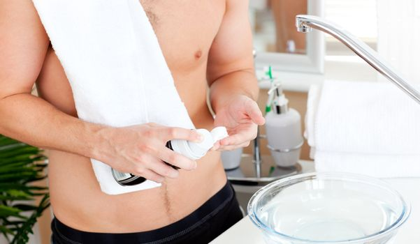Close-up of a young muscular man ready to shave in the bathroom