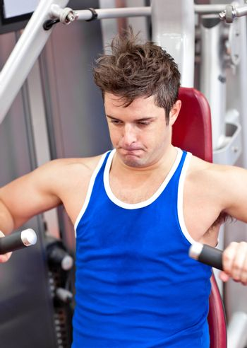 gorgeous man working hard on a bench press in a fitness centre