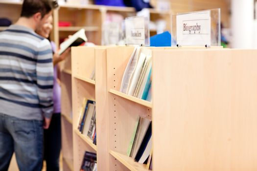 close-up of a bookshelves in a library with students reading boo
