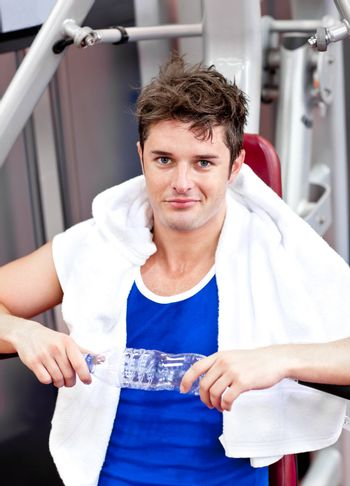 handsome man sitting on a bench press  after exercises