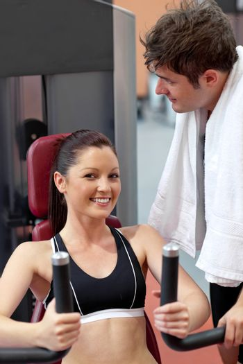 smiling woman sitting on a bench press with her boyfriend standi