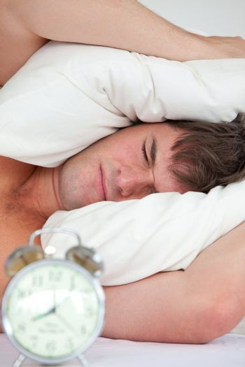 young male adult stressed by his alarm clock with his head under