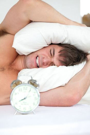 stressed man woken-up by his alarm clock putting his head under