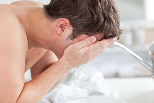 Cute caucasian man spraying water on his face after shaving in t